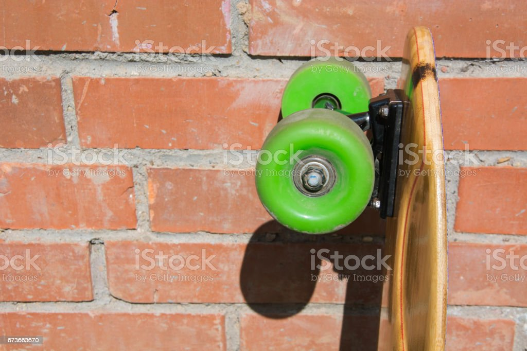 Longboard and green whels on the brick's background. Shallow depth of field. Close up. stock photo
