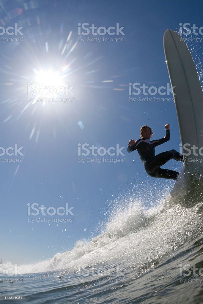 A longboard surfer riding the waves under the sun stock photo