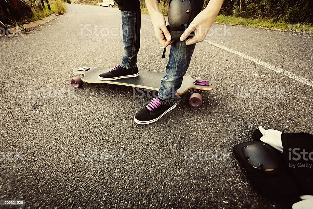 Longboarder strapping on her protective knee pads stock photo