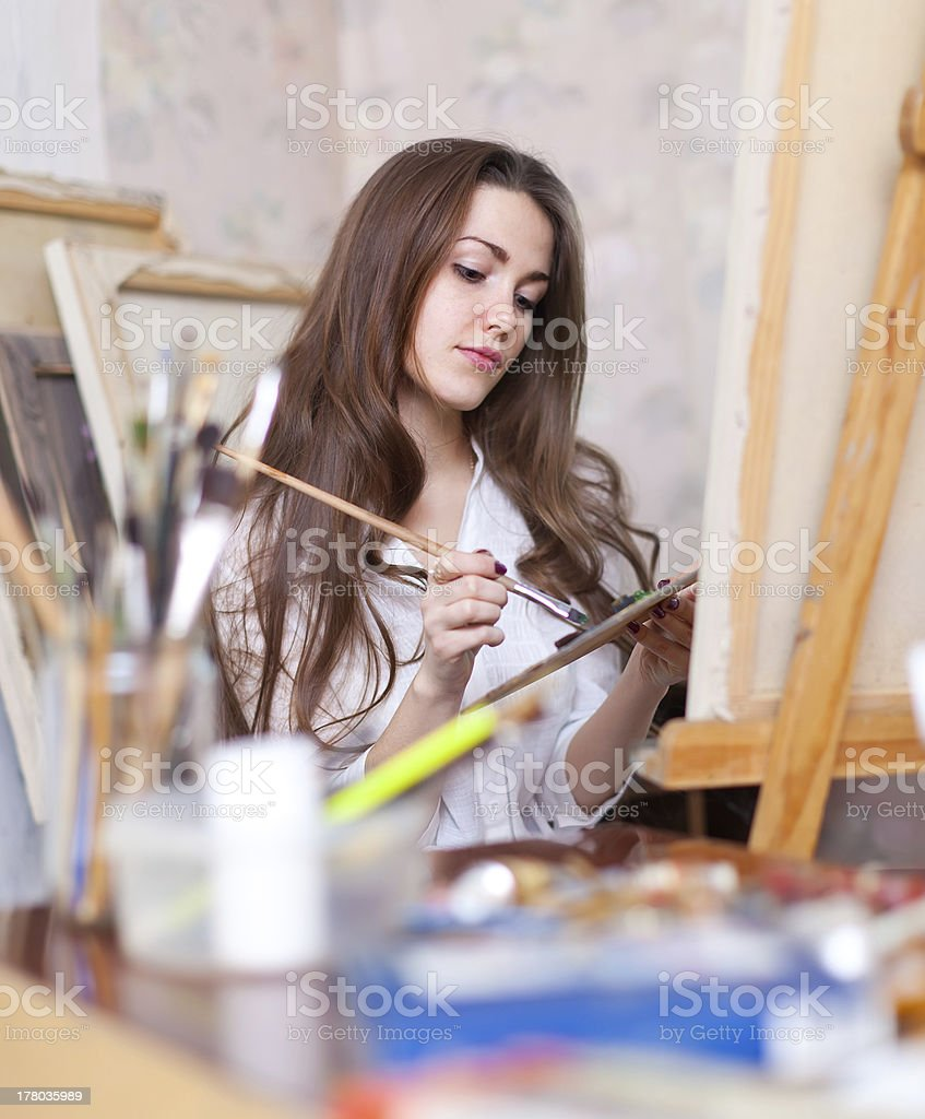 Long-haired  artist paints anything on canvas royalty-free stock photo