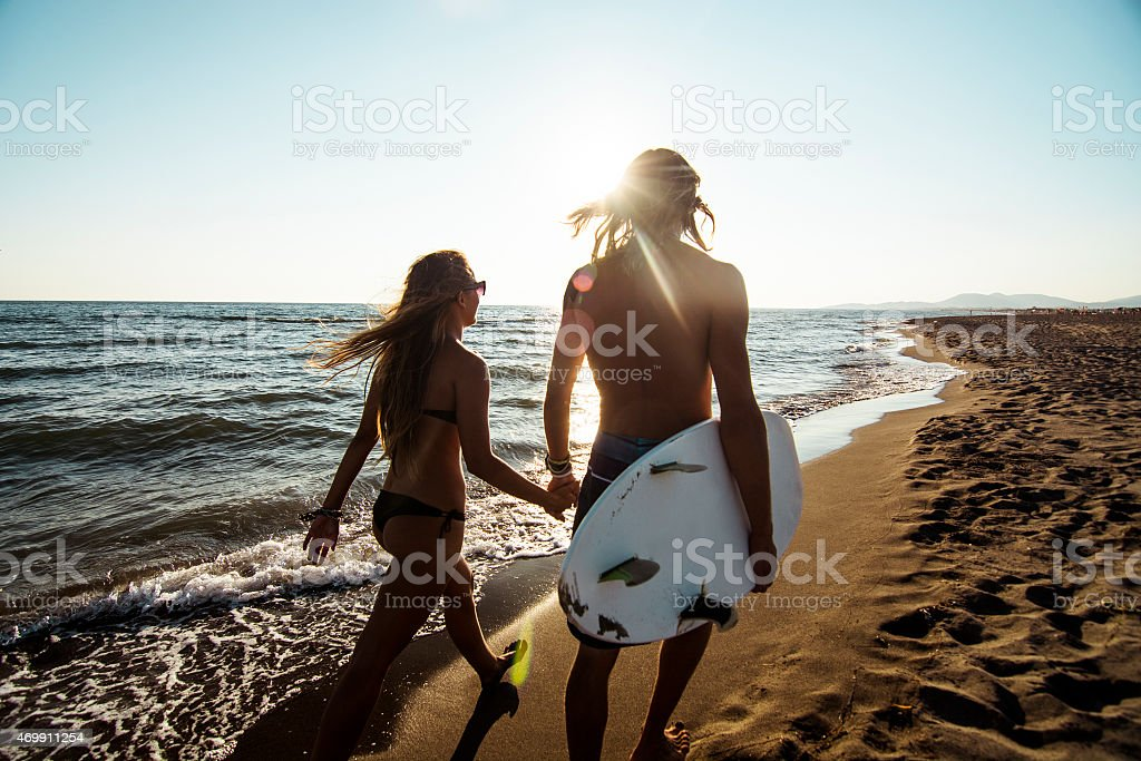 Long-haired couple with surfboard walking on the beach stock photo