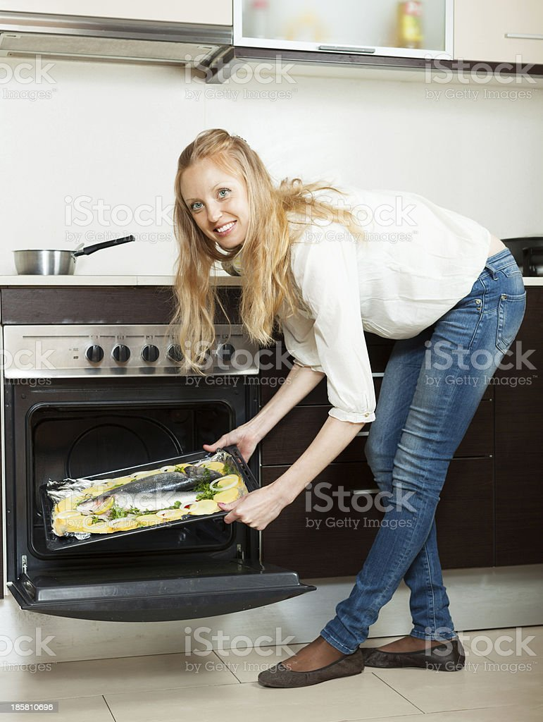 Long-haired girl cooking fish in oven royalty-free stock photo