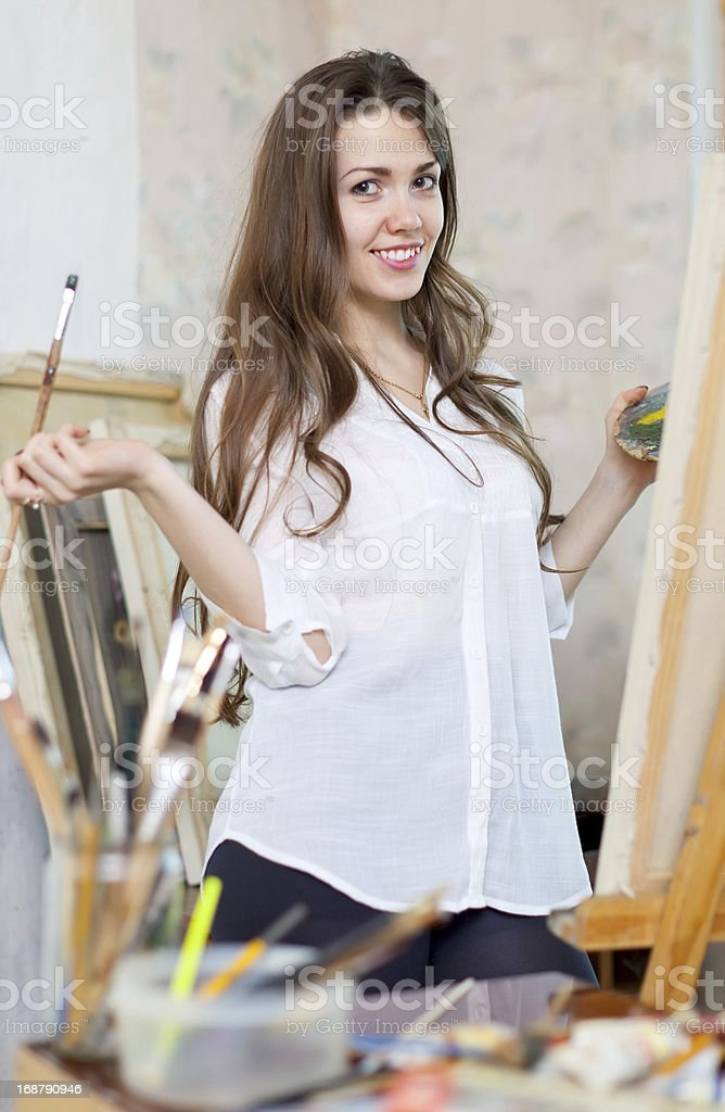 Long-haired girl paints  on easel royalty-free stock photo