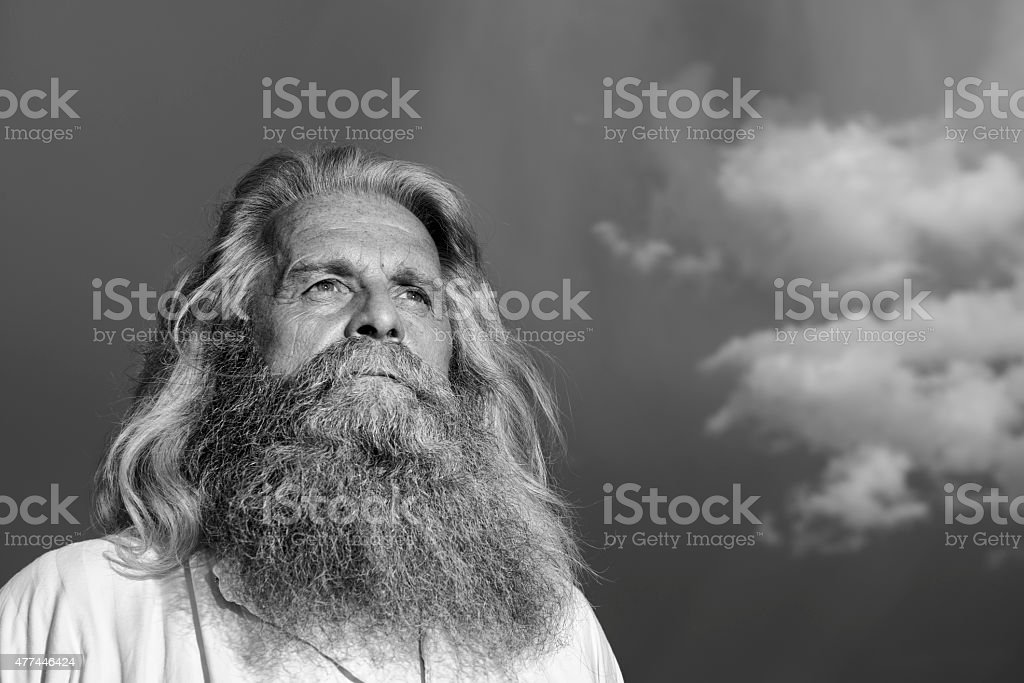 long-haired prophet standing in front of dramatic sky stock photo