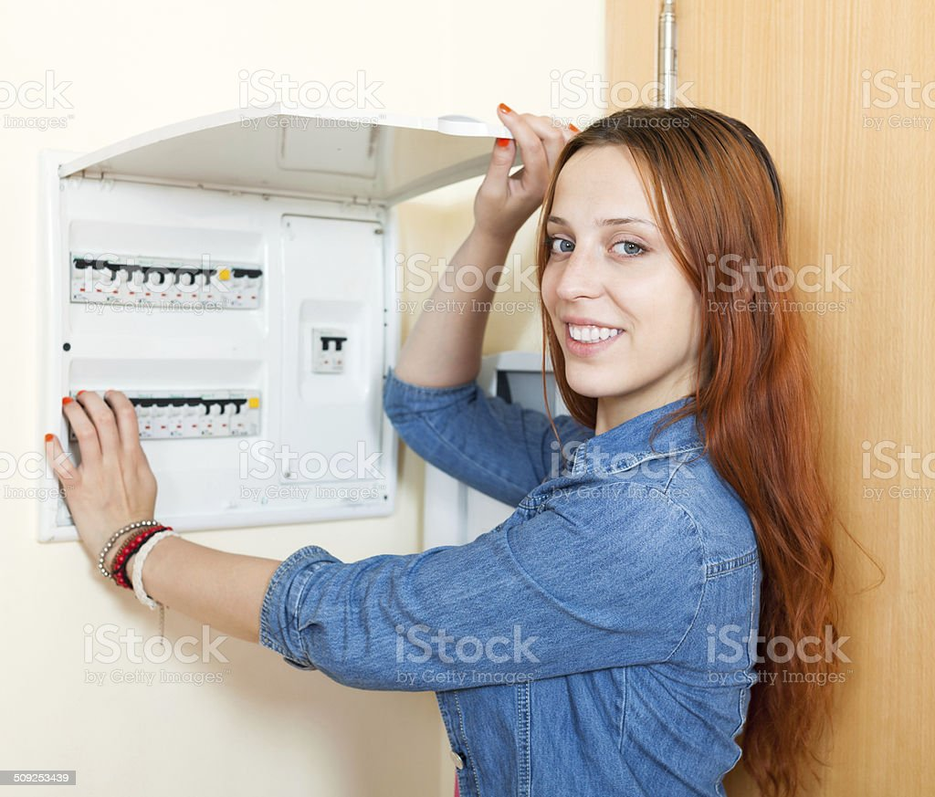 Long-haired smiling woman turning off the light-switch at power stock photo