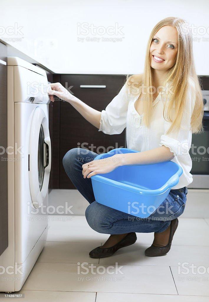 Long-haired woman using washing machine stock photo