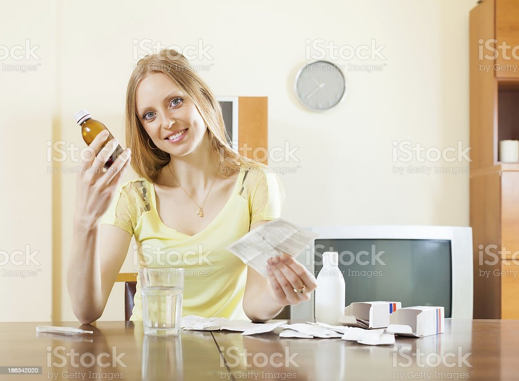 Long-haired woman with medications at table stock photo