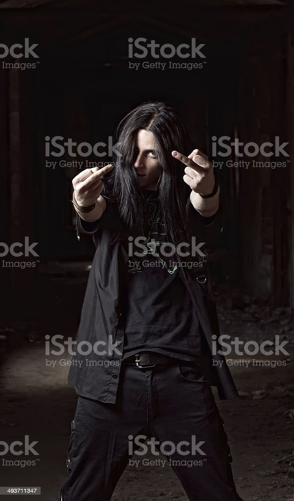 Long-haired young man making offensive gesture (middle fingers) stock photo