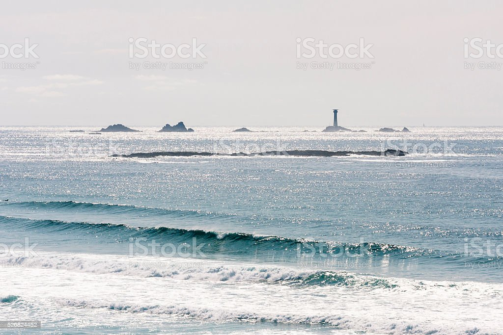 Longships lighthouse and waves breaking at Sennen beach in Cornwall stock photo