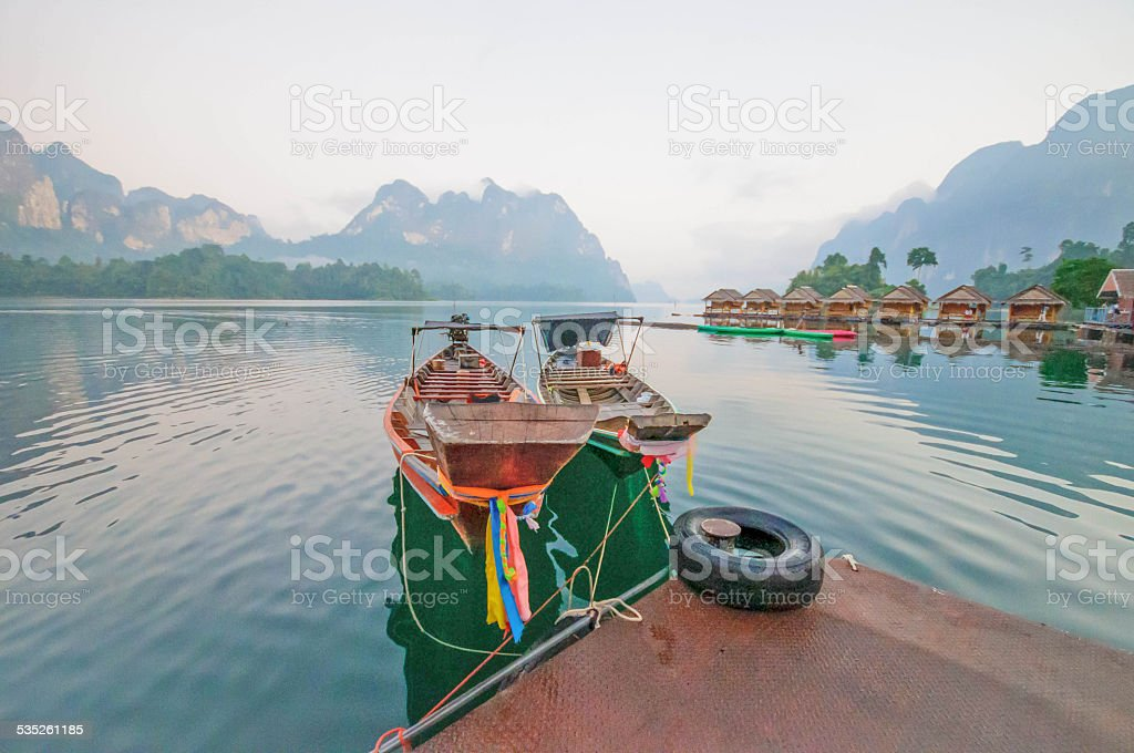 Long-tail boat and lakeside raft houses on Cheow Lan Lake stock photo