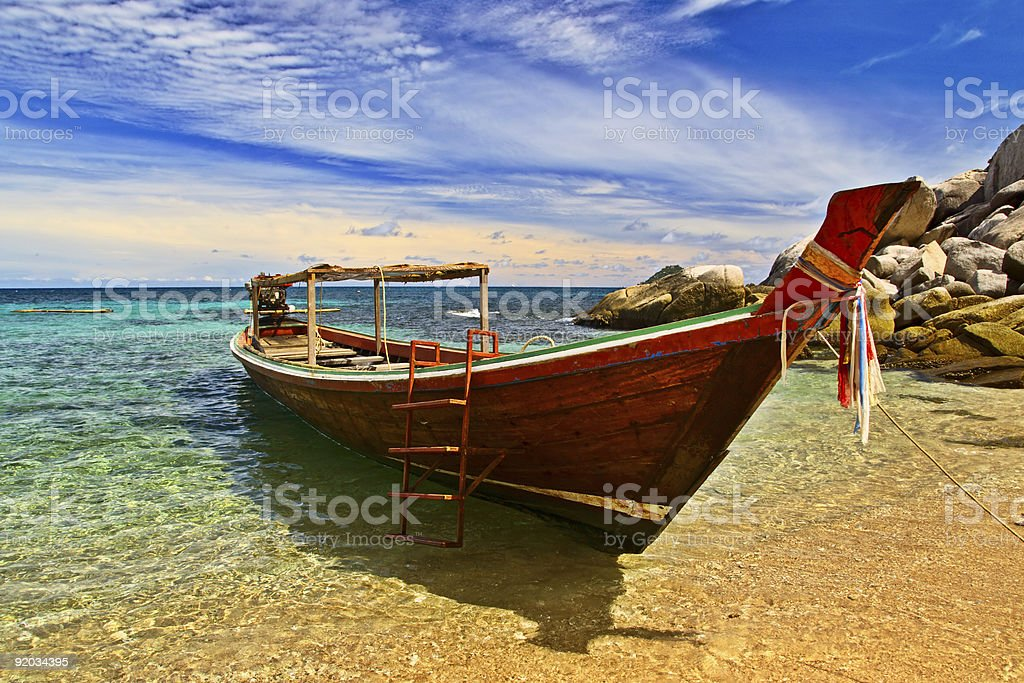 Longtail boat docked on the sand and crystal clear waters royalty-free stock photo