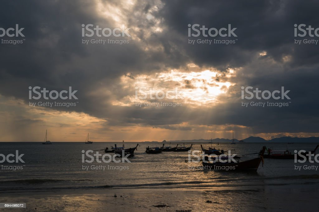 Longtail boat on beach with sunset background stock photo