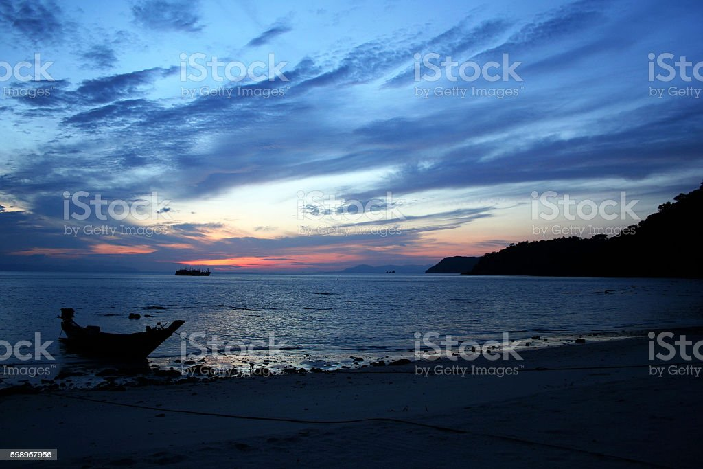 long-tail boat with sunrise on the beach. stock photo