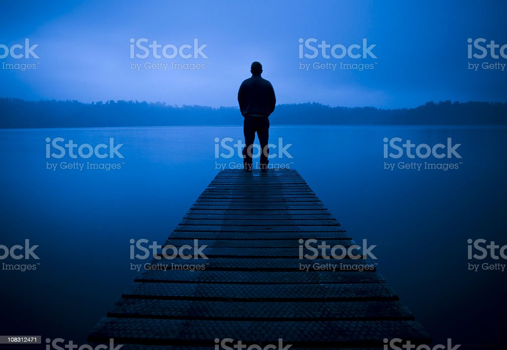 Lonley man stood at the end of a Pier royalty-free stock photo