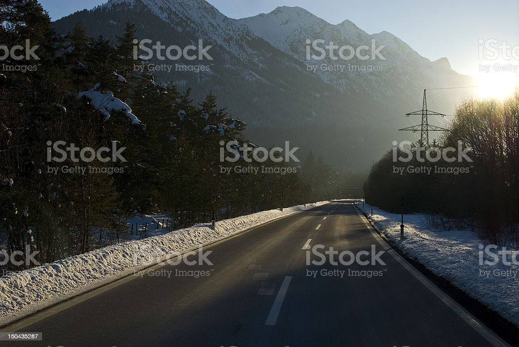 Lonley street in the evening with power pole and sun stock photo