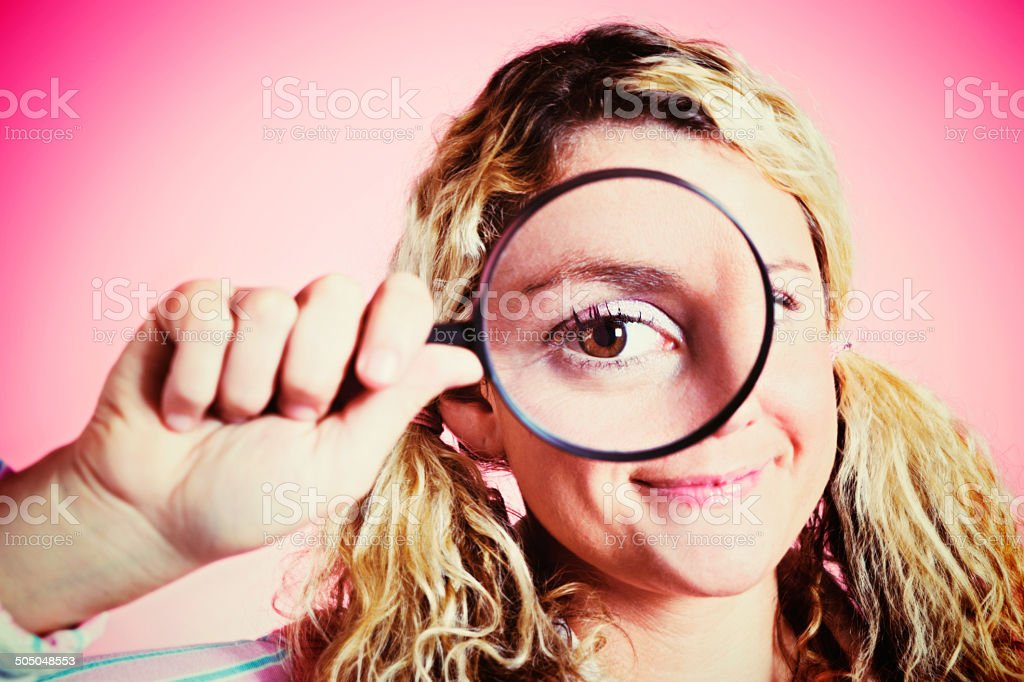 Look at that! Cute blonde geeks peers through magnifying glass royalty-free stock photo