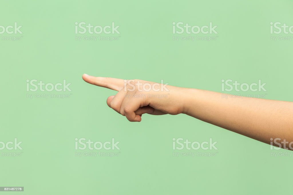 Look this! Hand finger pointing isolated on green background. Studio shot stock photo