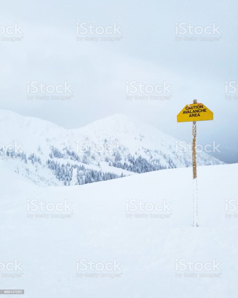Looking Across Vast, White Mountainscape with Danger Sign stock photo