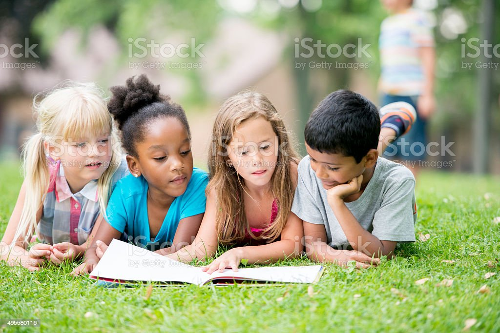 Looking at a Picture Book in the Park stock photo