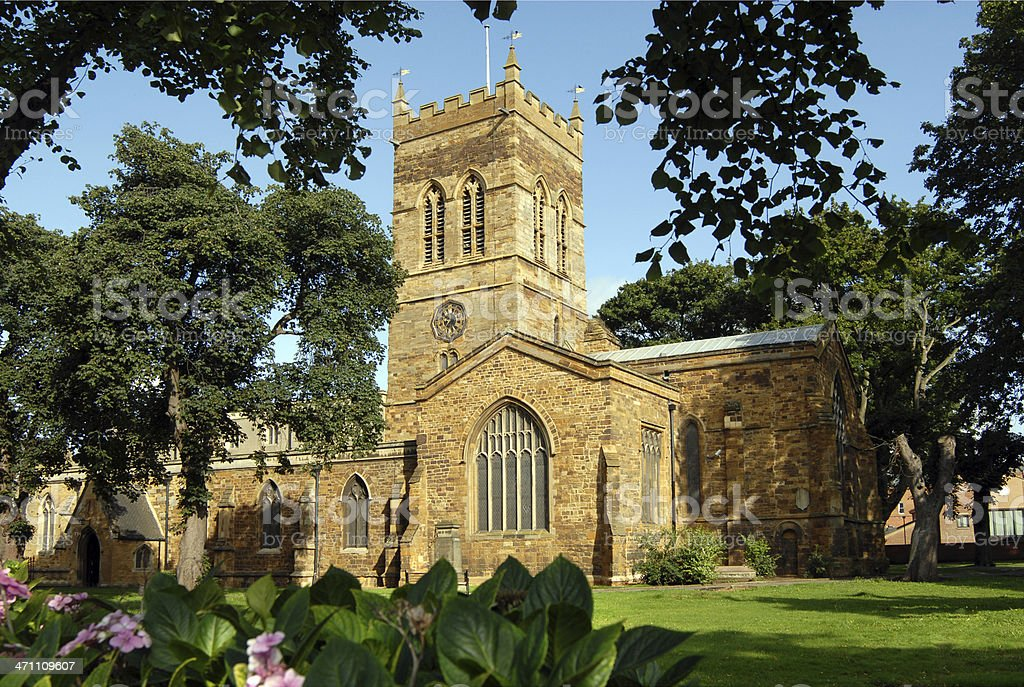 Looking at a stone church from the flower garden stock photo