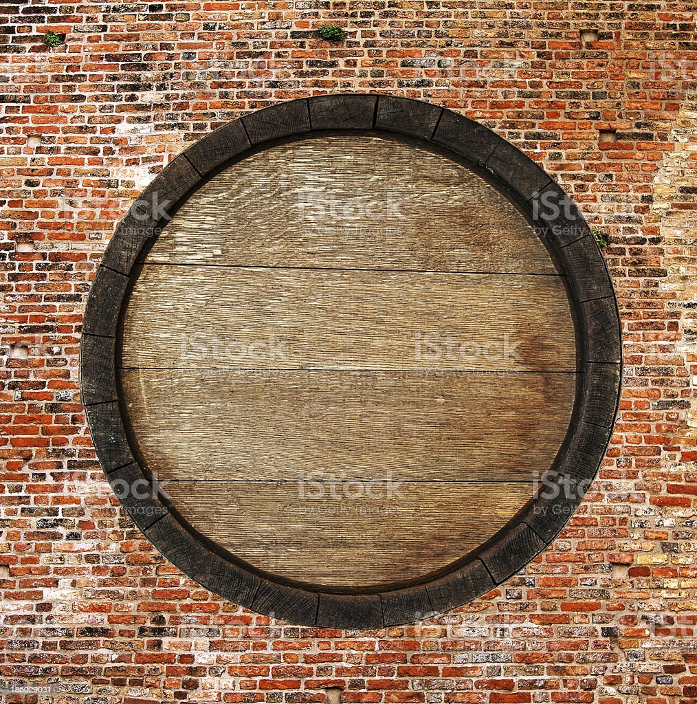 Looking at a wooden barrel surrounded by original brickwork stock photo