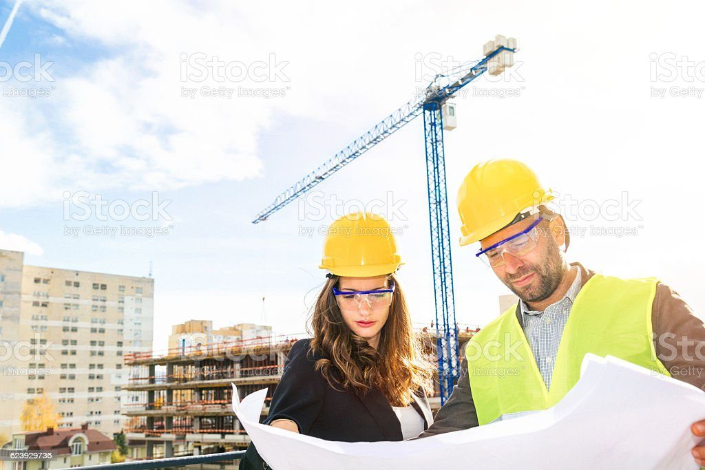 Looking at blueprints at the construction site stock photo