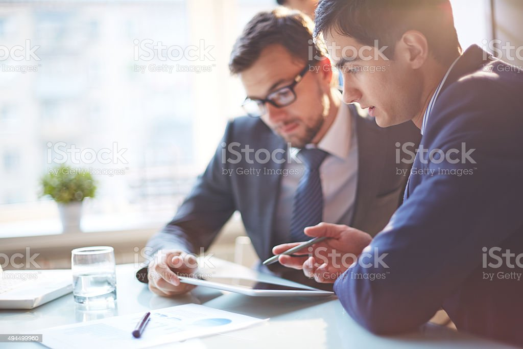 Young businessmen discussing data at meeting
