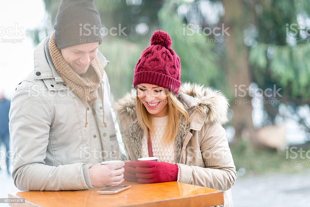 Looking at funny message on mobile phone stock photo