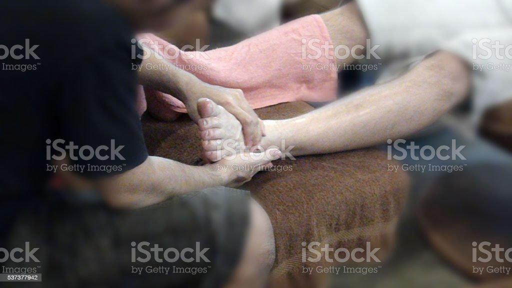 Looking At Human Hand Massaging Human Foot stock photo