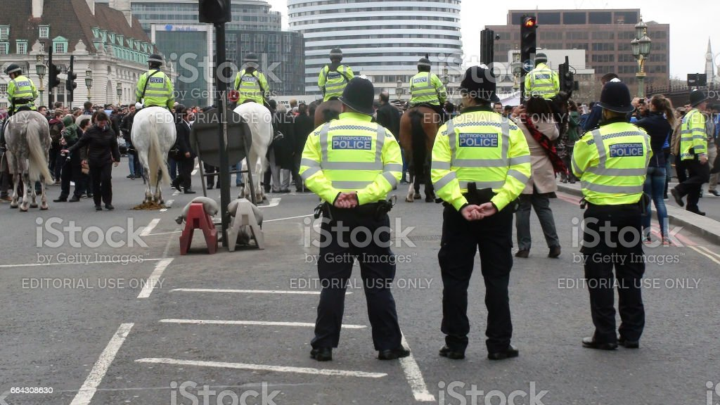 Looking At Police Officers Standing,People At Terrorist Attack Anniversary In Westminster.London stock photo