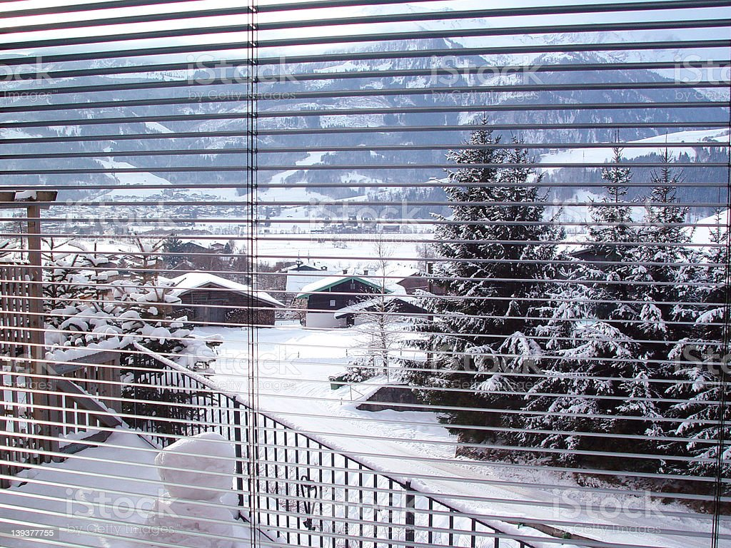 Looking at snow through windowblinds royalty-free stock photo
