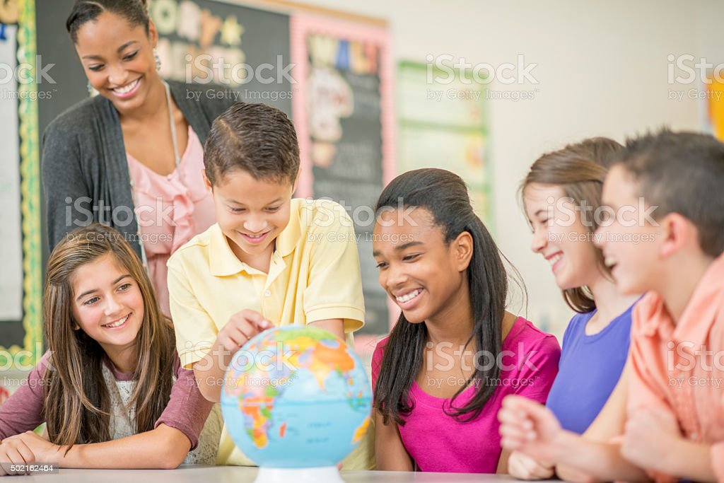 Looking at the Globe in Geography Class stock photo