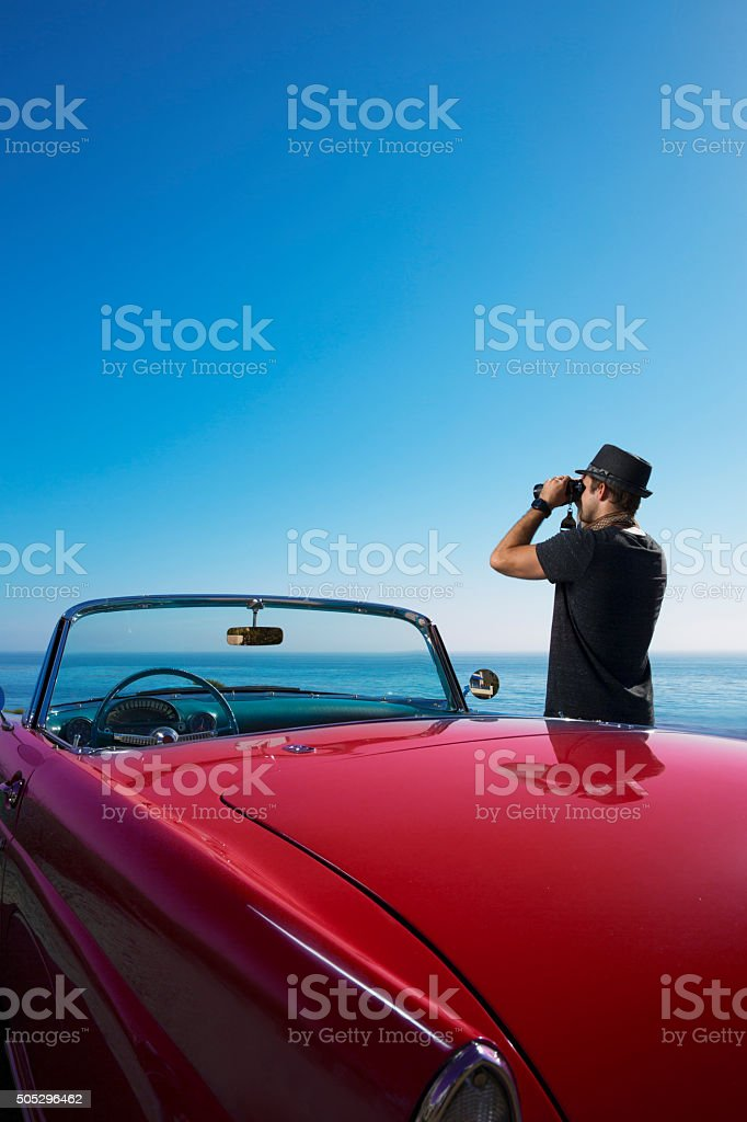 Looking at the Ocean by a Convertible Car with Binoculars stock photo
