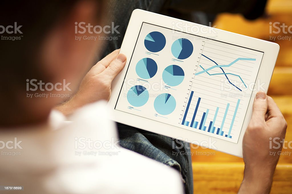 Looking at the stock market data on a tablet stock photo