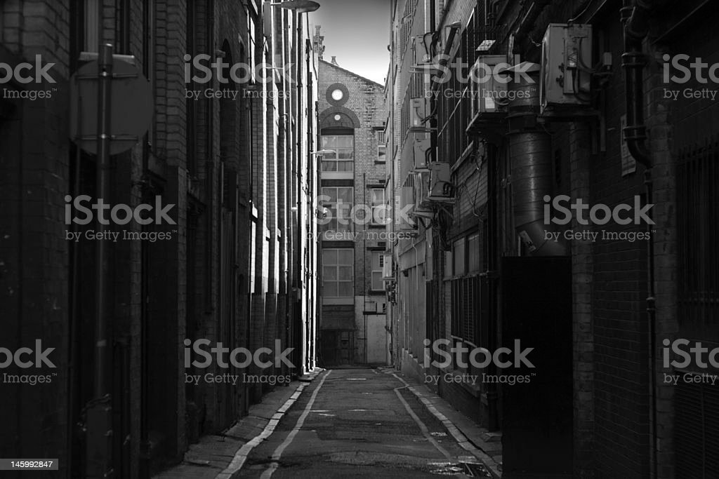 Looking down a long dark back alley stock photo