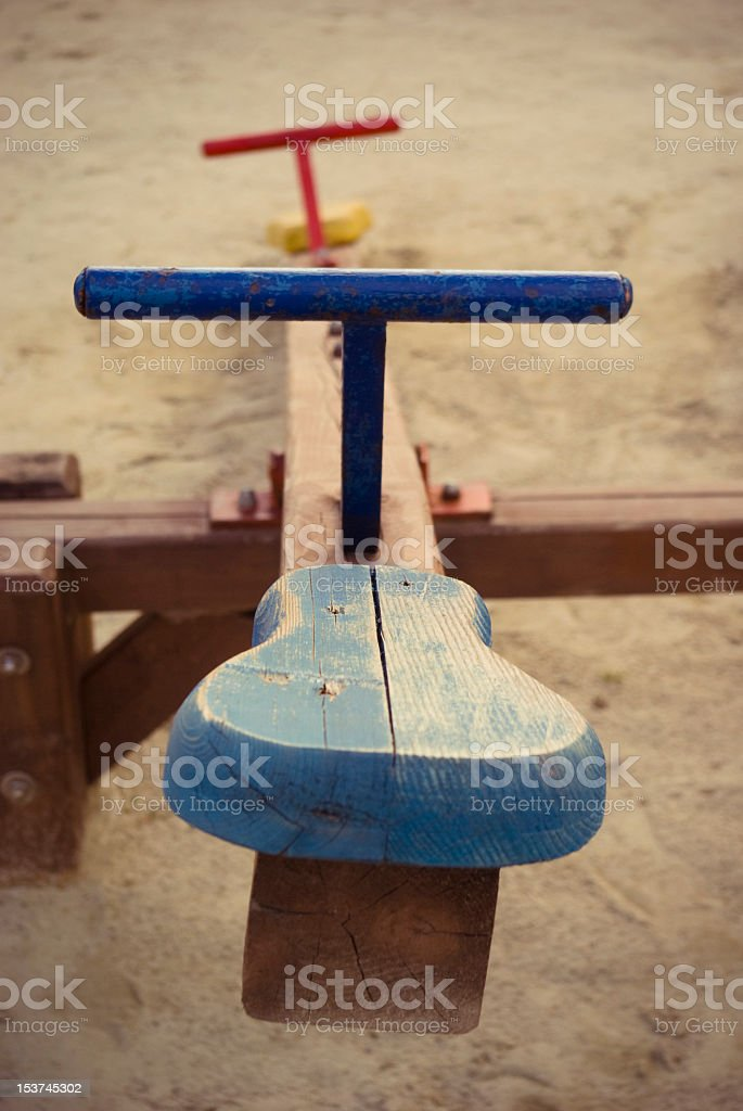 Looking down a wooden see-saw in a playground stock photo