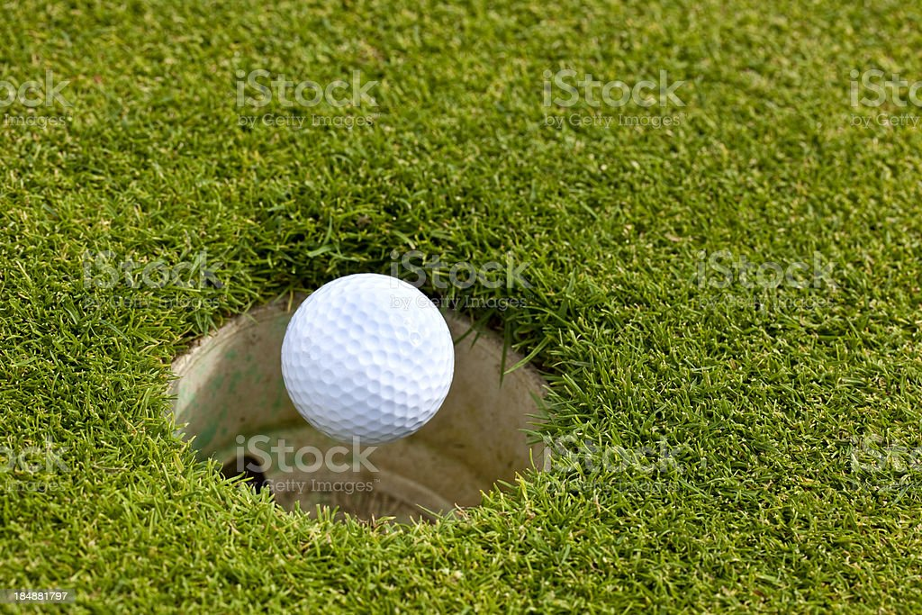 Looking down at golf ball falling into cup stock photo