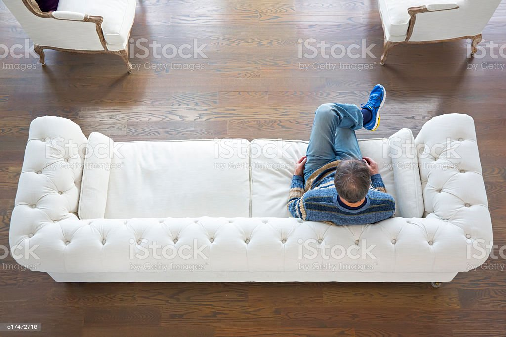 Looking down at Senior male in formal living room i stock photo