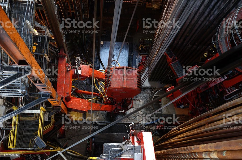 Looking down from derrick on traveling block above drill floor o stock photo