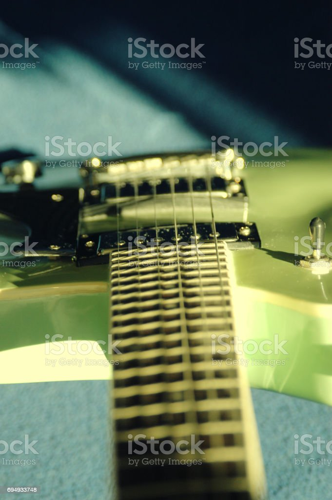 Looking down neck to body of electric guitar on blue background,...