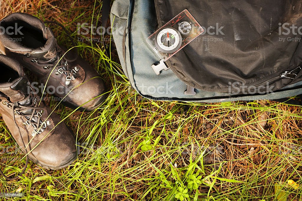 Looking down on hiking boots, backpack and compass, outdoors stock photo