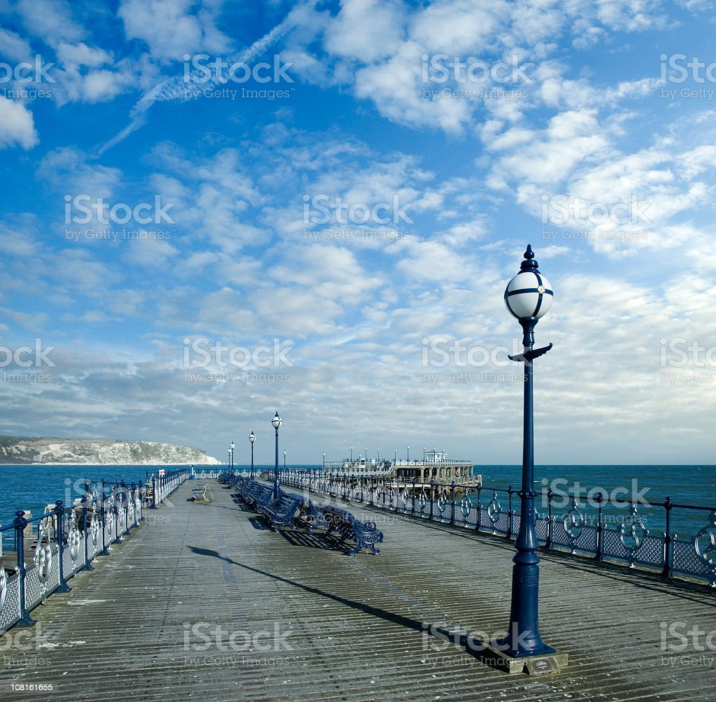 Looking Down Pier with Benches at Swanage in Dorset stock photo