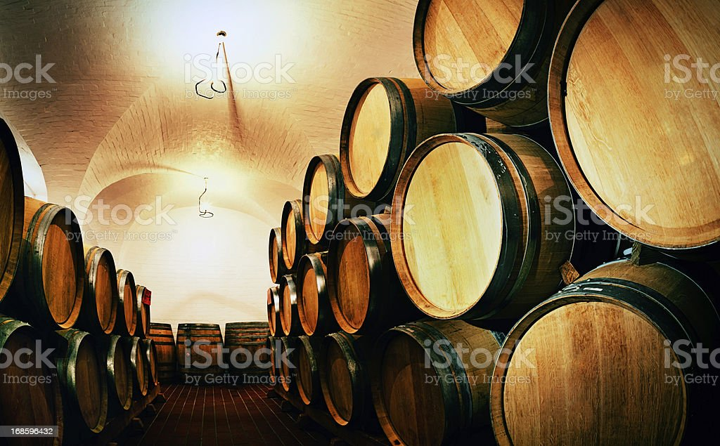 Looking down rows of stacked wine barrels in winery cellar royalty-free stock photo