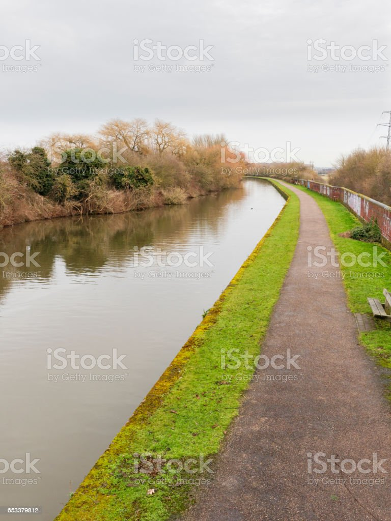 looking down the towpath of a quite treelined canal. stock photo