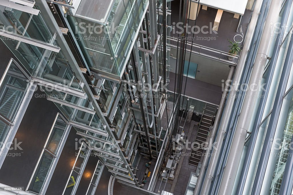 Looking downwards in a modern open elevator shaft stock photo