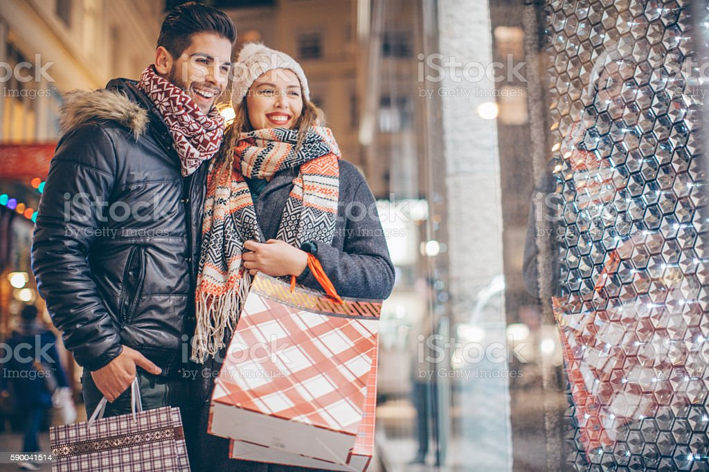 Couple window shopping outdoors in winter city street. Standing in...