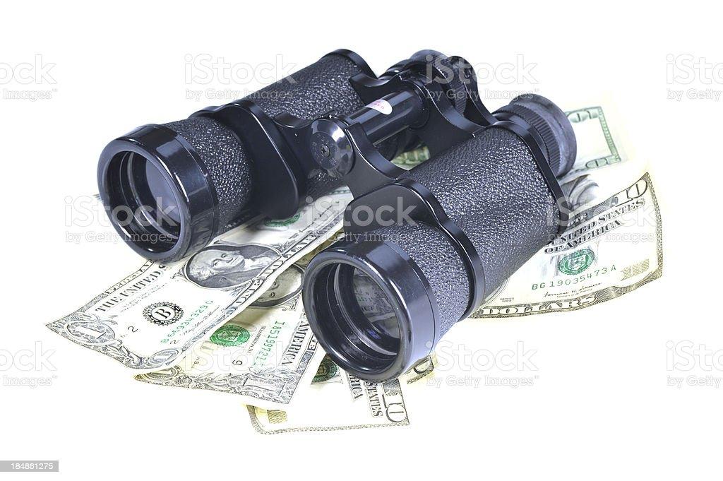 looking for money - binoculars on dollars stock photo