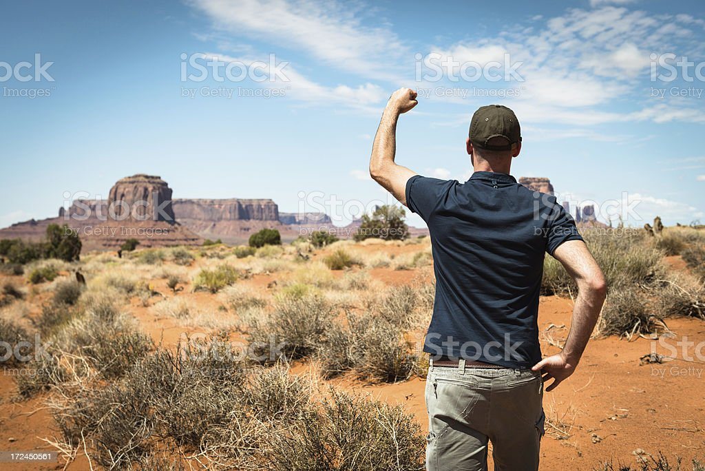 looking forward with arm raised on the Monument valley royalty-free stock photo