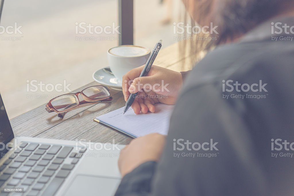 Looking from back of woman taking note without wearing glasses stock photo