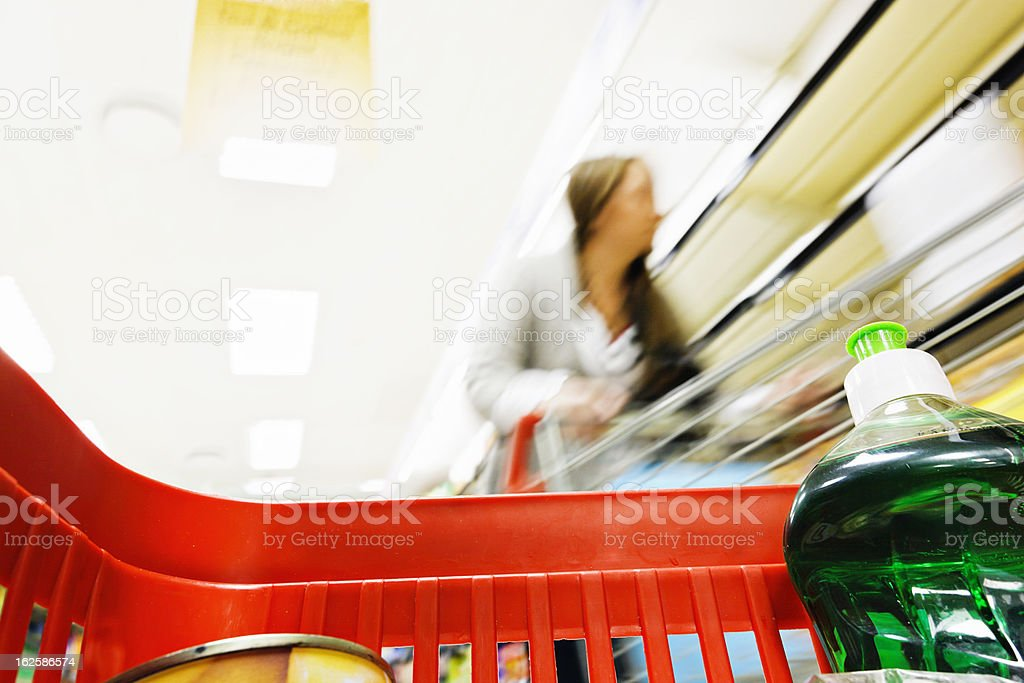 Looking from inside supermarket shopping basket at out-of-focus woman royalty-free stock photo